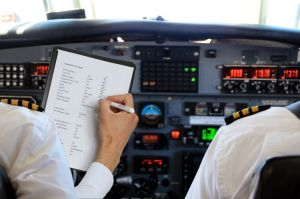 41720000 - two pilots in aircraft with a checklist